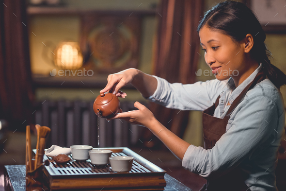 Smiling tea master pouring tea - Stock Photo - Images