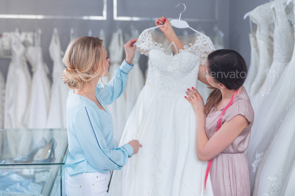 A young seller and customer with a wedding dress - Stock Photo - Images