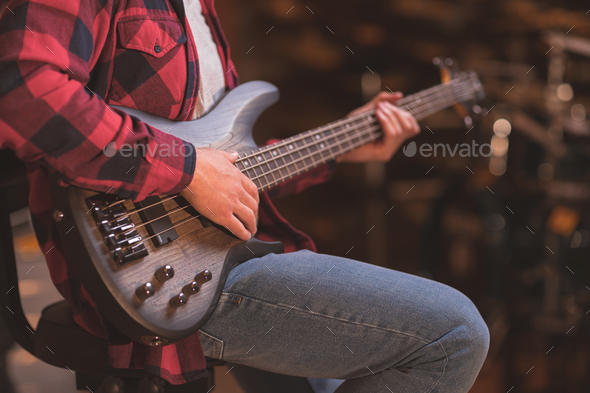 Young musician playing bass guitar - Stock Photo - Images