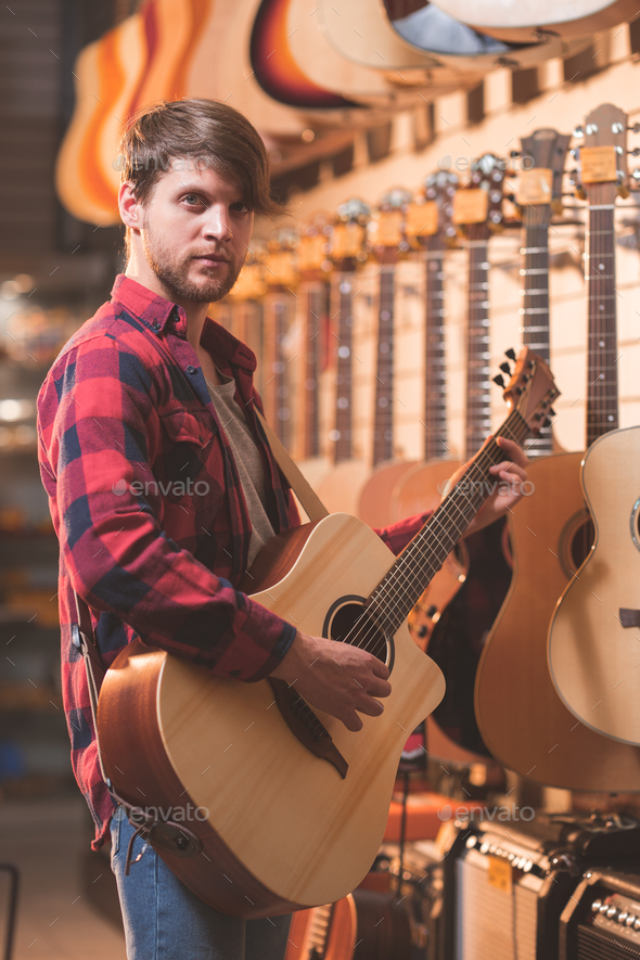 Young man in a music store - Stock Photo - Images