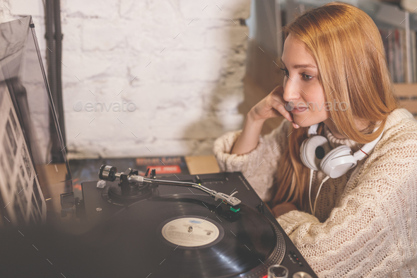 Young girl listening to a record - Stock Photo - Images