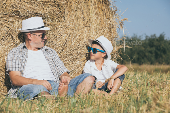 Father and son sitting in the park at the day time. - Stock Photo - Images