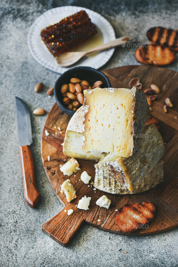 Cheese platter with cheese assortment, nuts, honey and bread - Stock Photo - Images