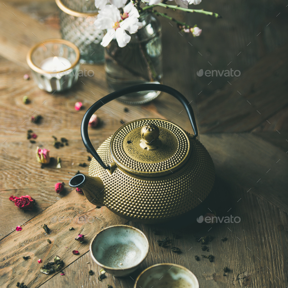 Golden iron teapot, cups, dried rose, candles, almond flowers - Stock Photo - Images