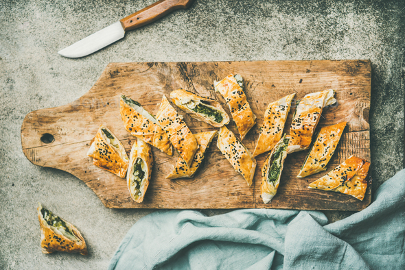 Freshly baked Turkish borek roll cut in slices, flat-lay - Stock Photo - Images