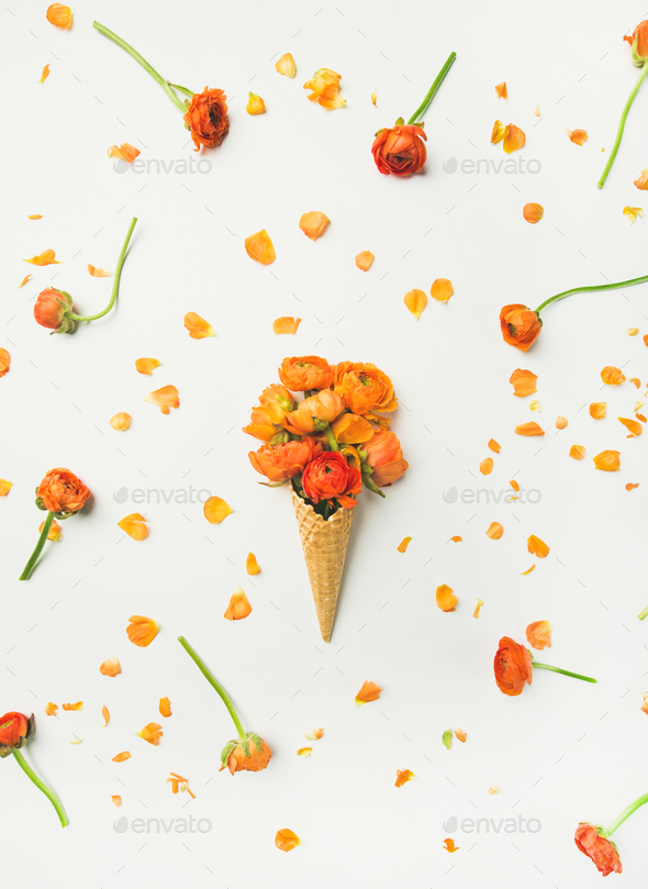 Waffle Cone With Orange Buttercup Flowers Over White Background