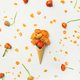 Waffle cone with orange buttercup flowers over white background - PhotoDune Item for Sale