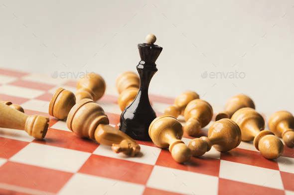 Black chess queen beats whites on chessboard - Stock Photo - Images