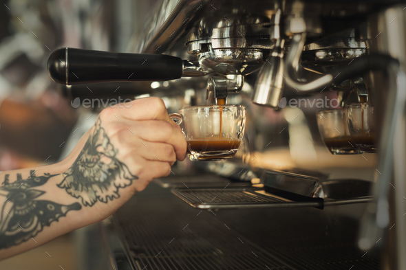 Closeup of female hand brewing espresso in professional coffee machine - Stock Photo - Images