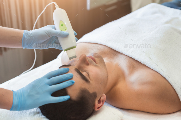 Man getting facial treatment at beauty salon - Stock Photo - Images
