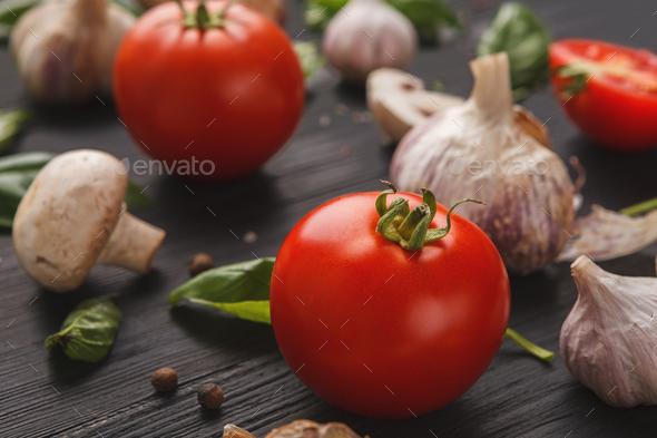Fresh tomatoes and garlic closeup on dark rustic wood - Stock Photo - Images