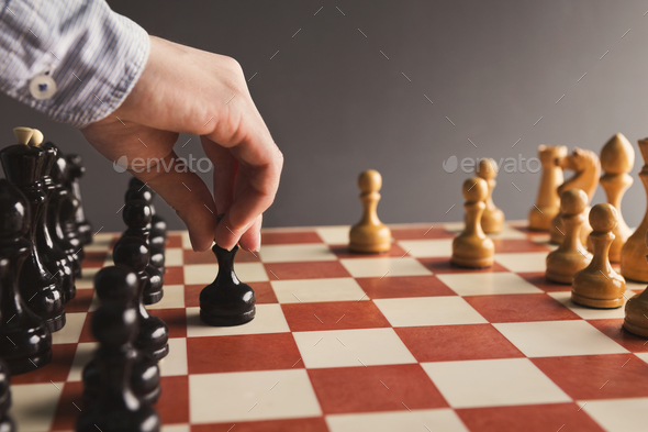Hand of player chess board game putting black pawn - Stock Photo - Images