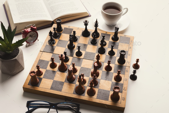 Wooden desk with chess play, book and coffee cup - Stock Photo - Images