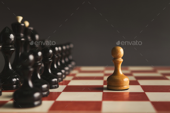 One pawn standing against set of black chess - Stock Photo - Images