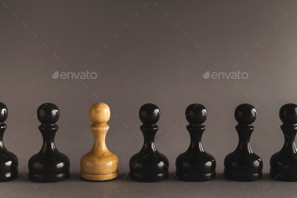 Line of black pawns with one white inside - Stock Photo - Images
