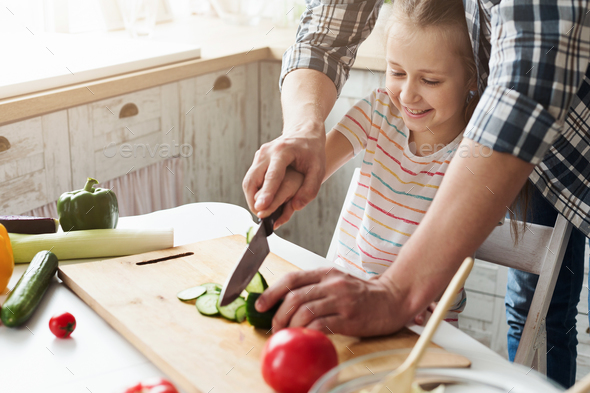 Little girl and dad having fun while cooking in kitchen - Stock Photo - Images
