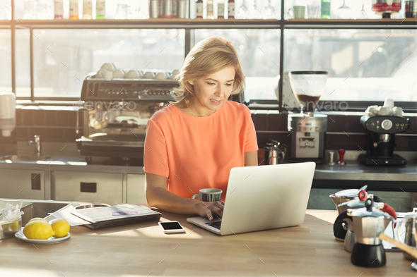 Happy middle-aged woman barista working on laptop - Stock Photo - Images