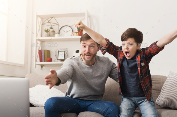 Father and son watching football on TV at home - Stock Photo - Images