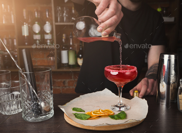 Hands of barman preparing cocktail at bar counter - Stock Photo - Images