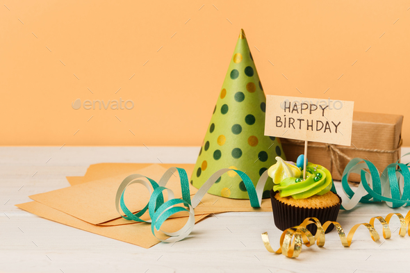 Delicious cupcake and gift on yellow background - Stock Photo - Images