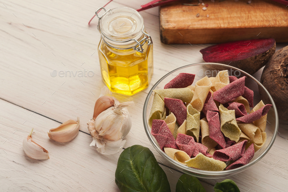 Italian pasta in bowls and laurel leaf on white wood - Stock Photo - Images