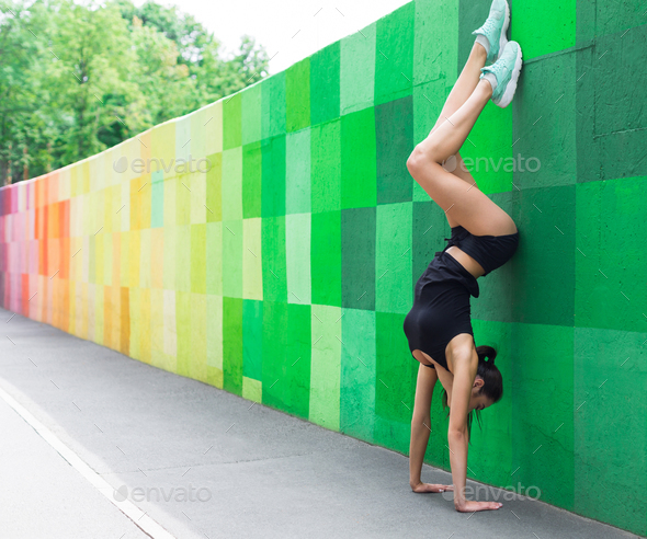 Young woman doing handstand on city street - Stock Photo - Images