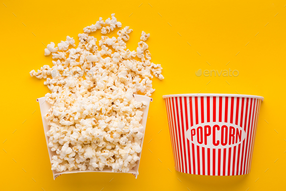 Popcorn bucket cut in half on yellow background - Stock Photo - Images
