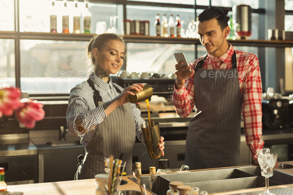 Male and female bartenders at coffee shop counter - Stock Photo - Images