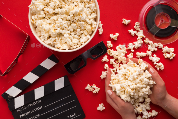 Clapperboard, 3D glasses and popcorn on red background - Stock Photo - Images