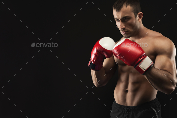 Muscular man in boxing gloves at black background - Stock Photo - Images