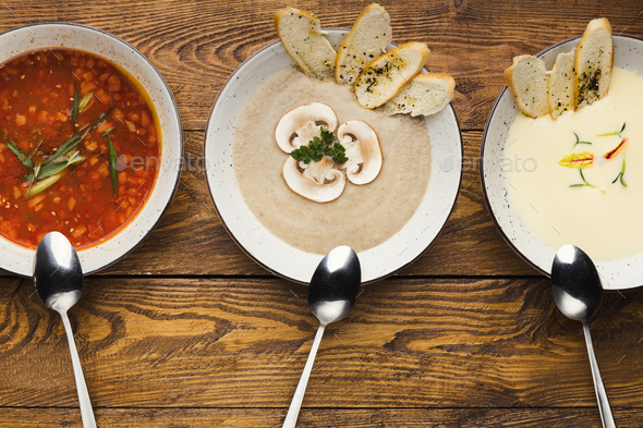 Set of various soups on wooden background, top view - Stock Photo - Images