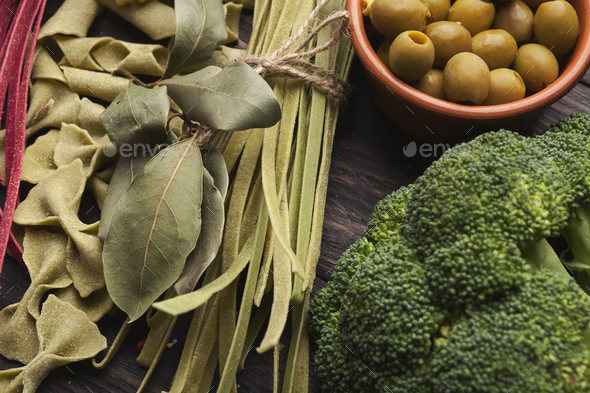 Green italian pasta and cooking ingredients on wooden table - Stock Photo - Images