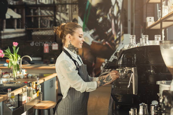 Tattooed barista making coffee in professional coffee machine - Stock Photo - Images