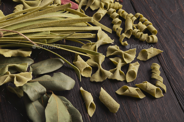 Assorted italian green pasta on wooden background - Stock Photo - Images