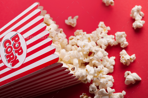 Bucket of popcorn on red background - Stock Photo - Images