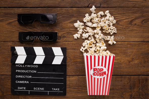 Clapperboard, 3D glasses and popcorn on wooden background - Stock Photo - Images