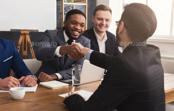 Business handshake at multiethnic office meeting - Stock Photo - Images