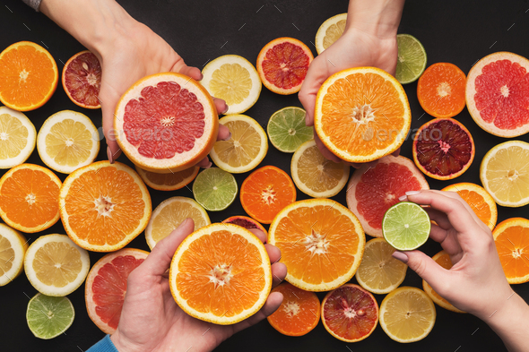 Hands choosing citrus fruits, top view - Stock Photo - Images