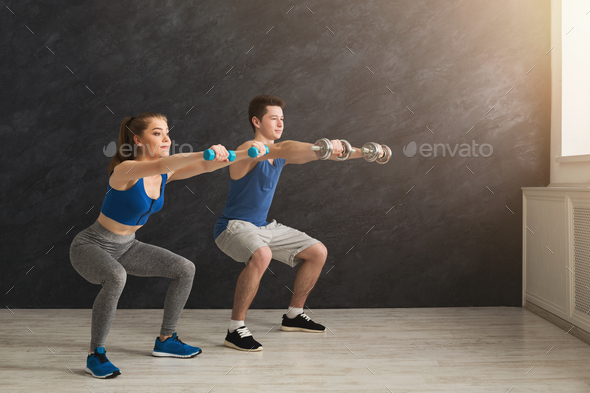 Young couple in sportswear doing squat - Stock Photo - Images