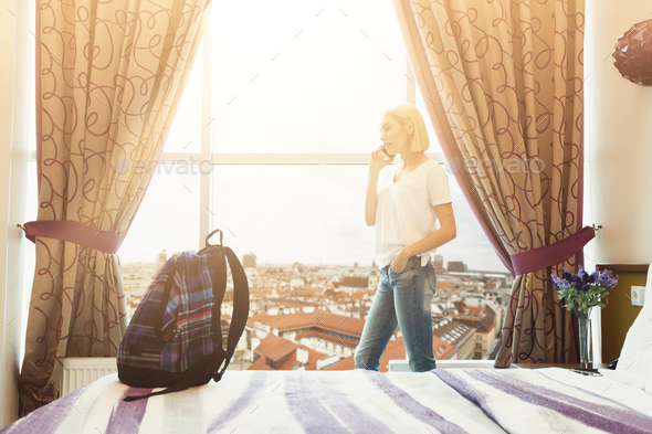 Woman standing near window in hotel room - Stock Photo - Images
