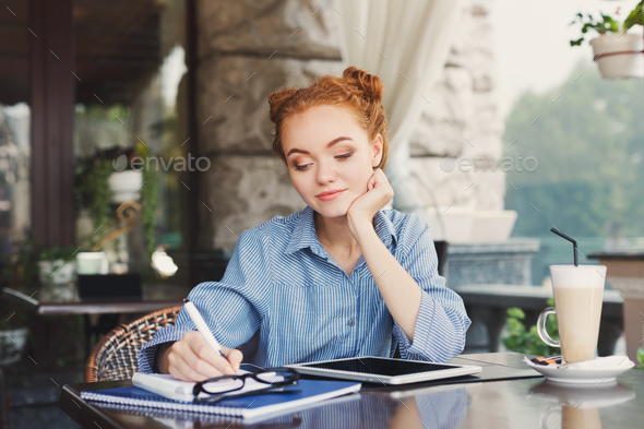 Young redhead girl making notes in a notebook - Stock Photo - Images