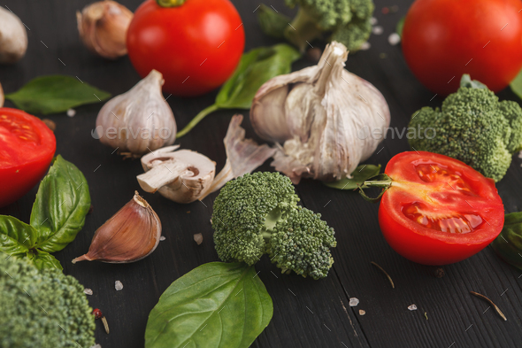 Fresh tomatoes and garlic closeup on dark rustic wood - Stock Photo - Images