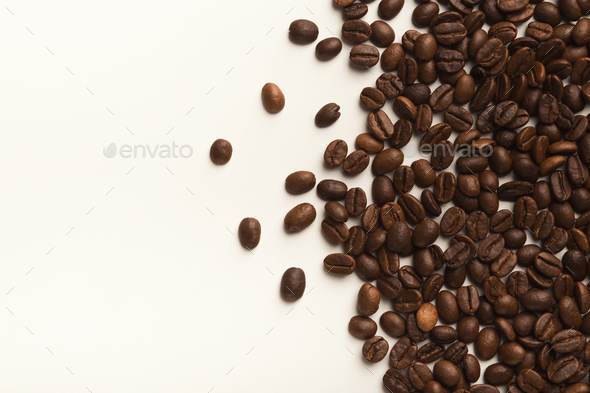 Heap of brown coffee beans isolated on white - Stock Photo - Images
