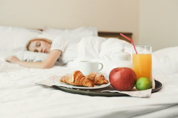 Closeup of breakfast in front of sleeping woman - Stock Photo - Images