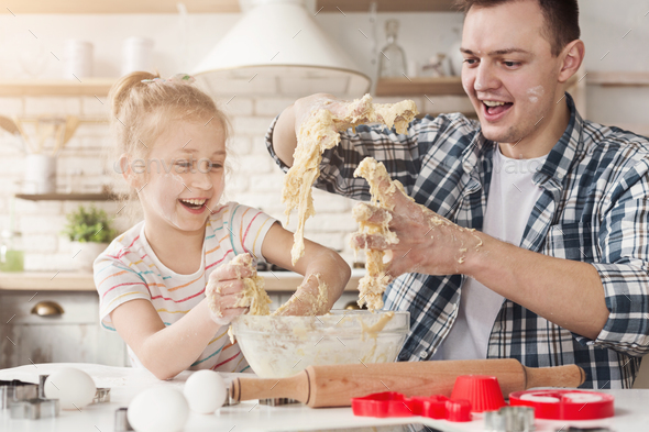 Cute little girl and father kneading dough and smiling - Stock Photo - Images