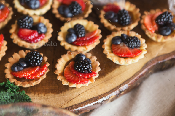 Small tartalettes with berries on wooden cutting board - Stock Photo - Images