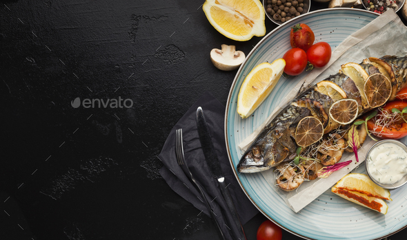Fried fish with vegetables served at restaurant on black table - Stock Photo - Images