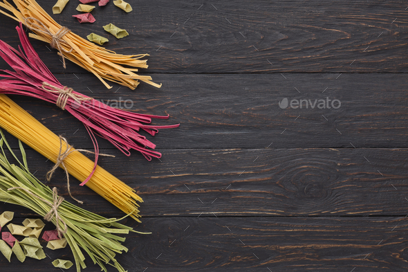 Pile of purple and green fettuccine pasta on wooden background - Stock Photo - Images