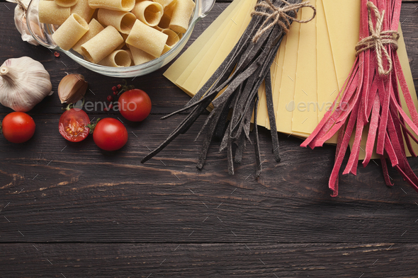Red italian pasta and cooking ingredients on wooden table - Stock Photo - Images