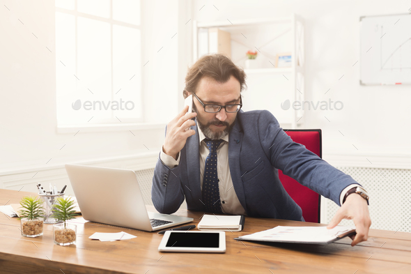 Serious businessman talking on mobile phone - Stock Photo - Images